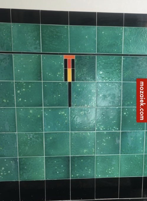 detail tegellambrisering met rood oranje geel en zwart en gewolkte groene tegels